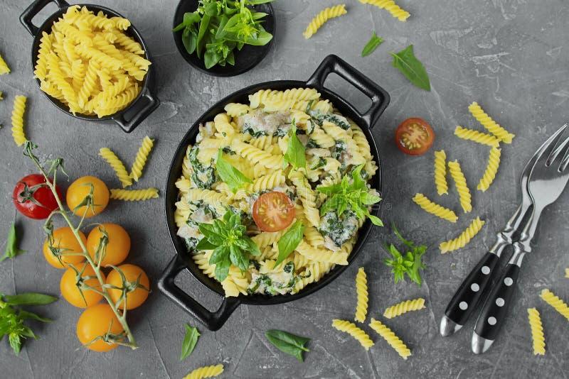 Massa de Fusilli com espinafres, cereja, bacon em pratos pretos fotografia de stock