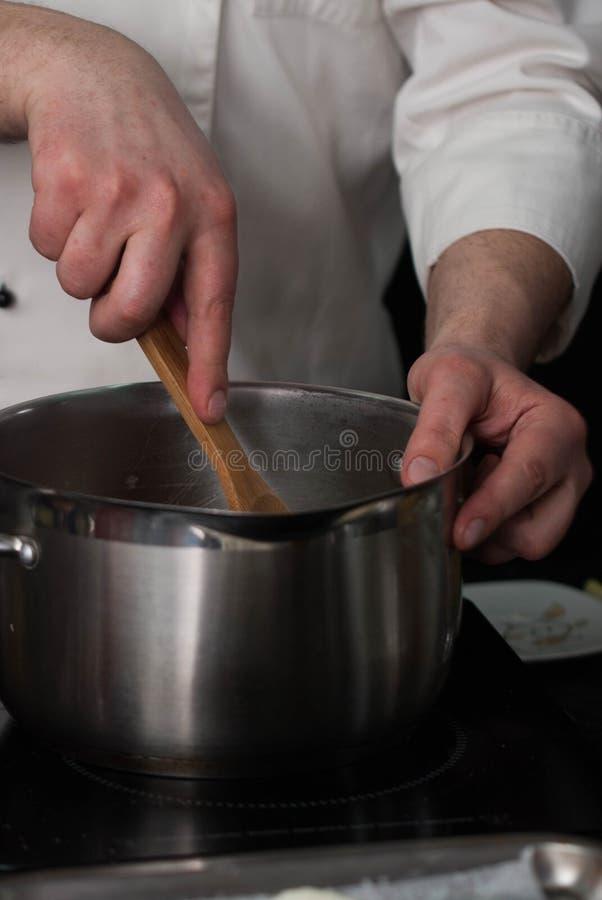 Massa de Hands Mixing Pancake do cozinheiro chefe na bacia do metal Componentes de mistura Panquecas do cozimento em andamento Im fotos de stock royalty free