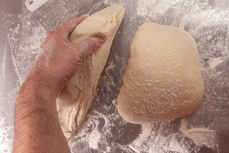 Massa de pão feito à mão que está sendo preparada imagem de stock