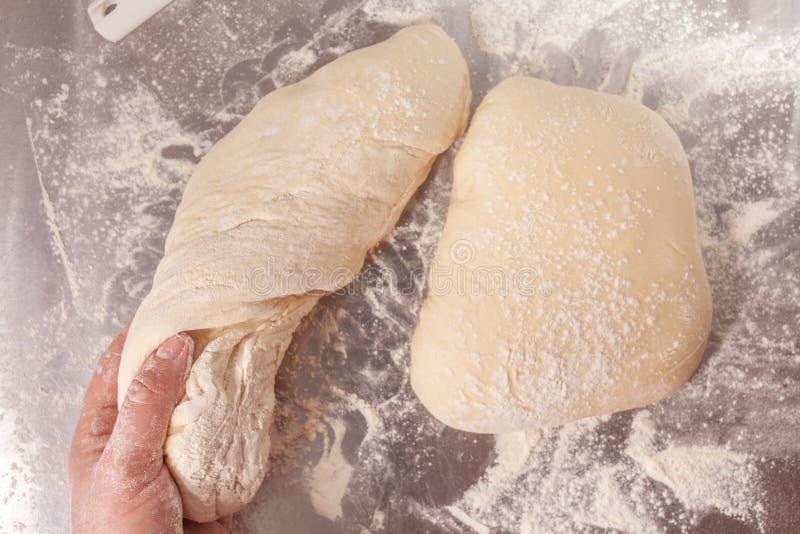 Massa de pão feito à mão que está sendo preparada foto de stock