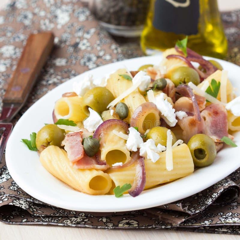 Massa de Rigatoni com bacon, azeitonas verdes, queijo de feta, cebola vermelha fotos de stock royalty free