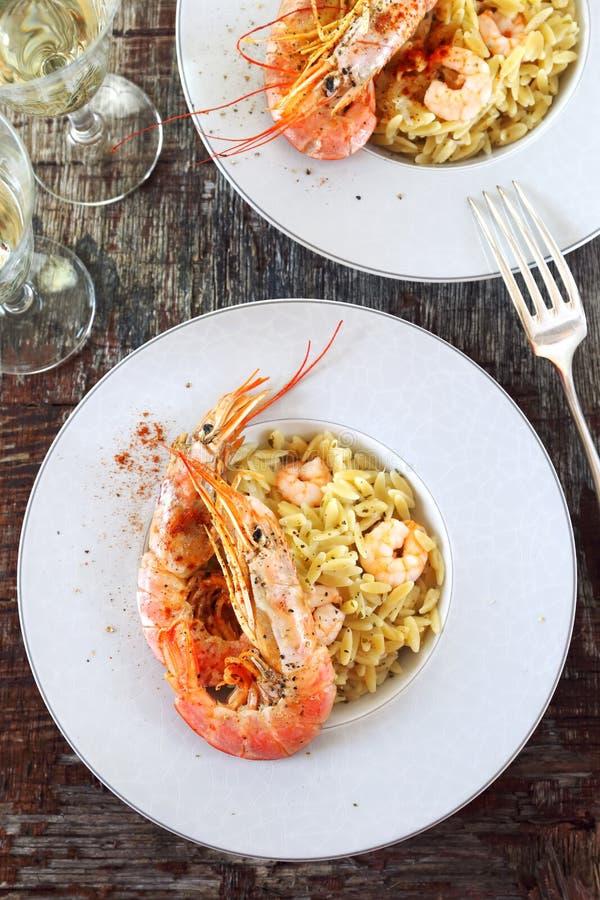 Massa de Risoni no risoto com camarões, as lagostas vermelhas e vinho branco fotos de stock