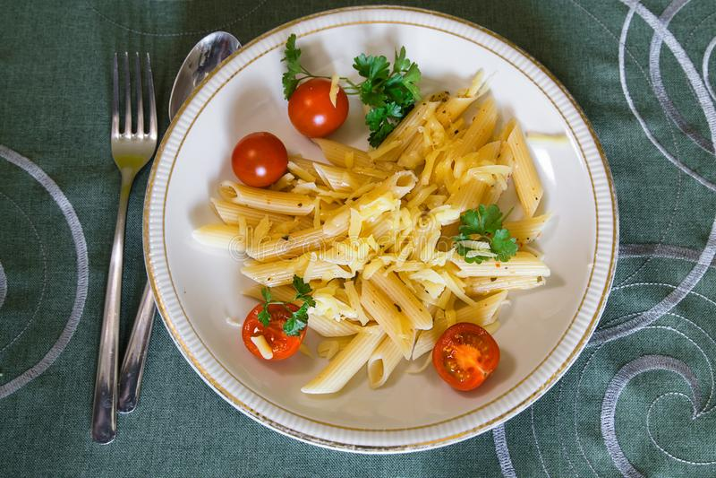 Massa deliciosa do penne com tomates e queijo de cereja na placa branca Forquilha e colher imagem de stock