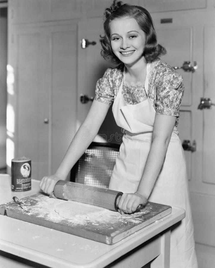 Massa desenrolando da jovem mulher na cozinha (todas as pessoas descritas não são umas vivas mais longo e nenhuma propriedade exi foto de stock royalty free