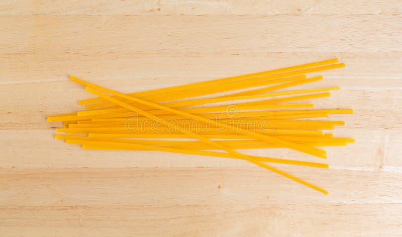 Massa do milho do Linguine na placa de corte imagem de stock royalty free
