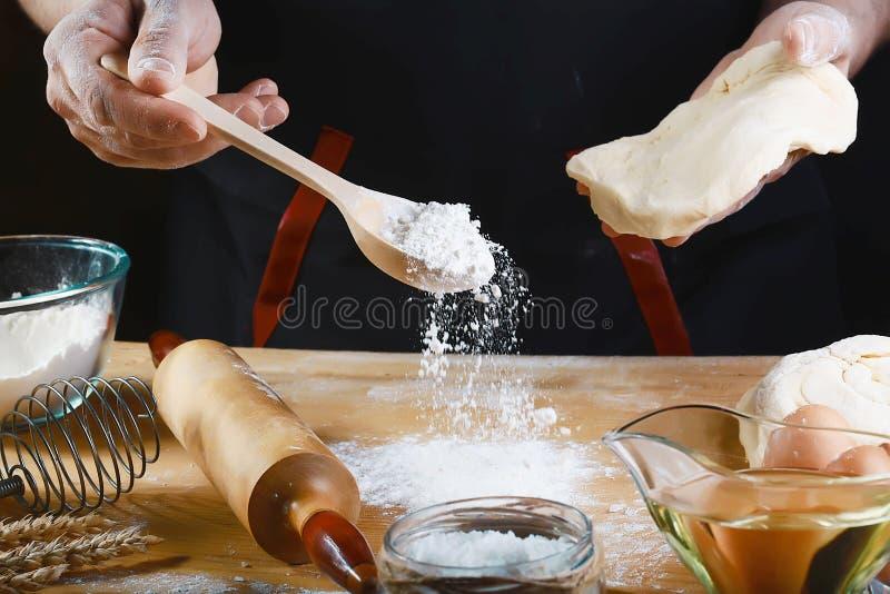 Massa do rolamento do padeiro com os ingredientes da receita do pão, da pizza ou da torta da farinha com mãos, alimento no fundo  imagens de stock royalty free