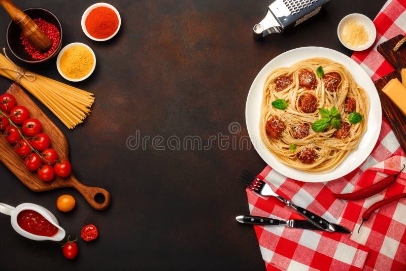 Massa dos espaguetes com almôndegas, molho de tomate da cereja e queijo no fundo oxidado fotos de stock royalty free