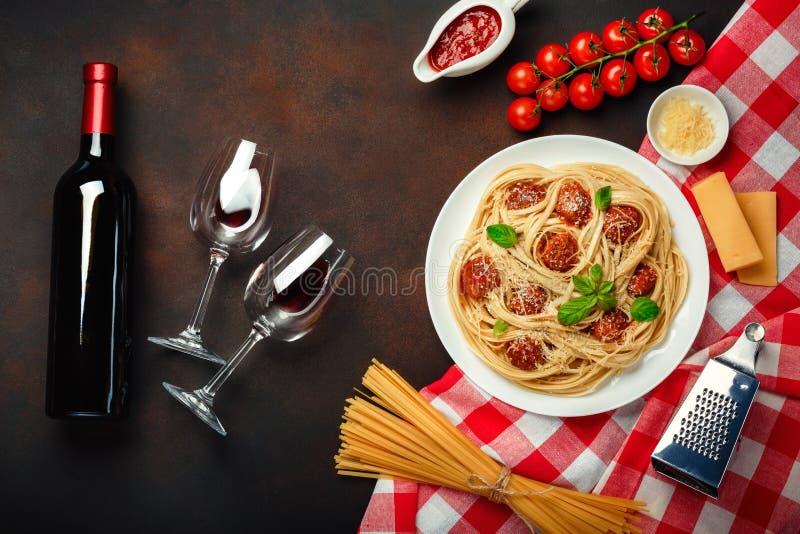 Massa dos espaguetes com almôndegas, molho de tomate da cereja, queijo, copo de vinho e garrafa no fundo oxidado fotografia de stock