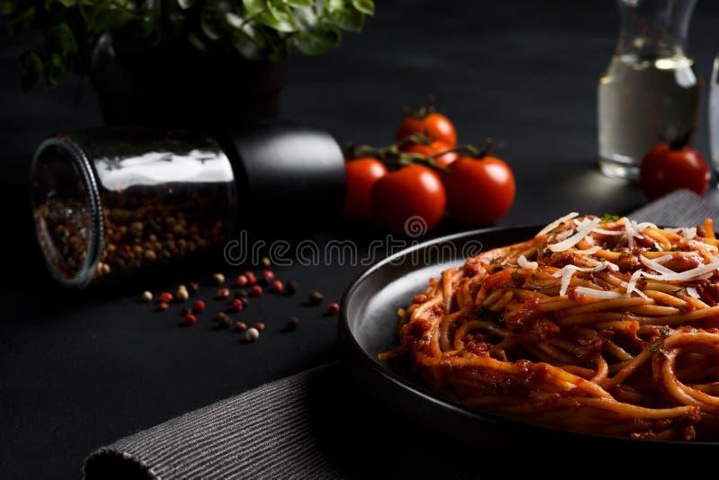 Massa dos espaguetes com molho de tomate, o tomate fresco e o queijo no fundo escuro imagem de stock