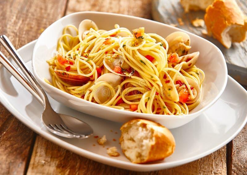 Massa dos espaguetes com os moluscos servidos com rolo de pão foto de stock