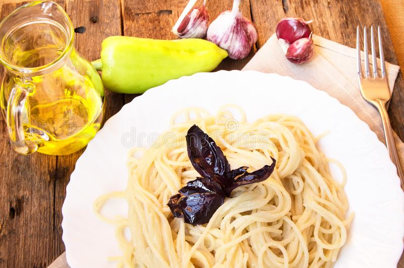 Massa dos espaguetes em uma placa branca com manjericão em uma tabela de madeira velha com vegetais e azeite em um jarro de vidro imagens de stock royalty free
