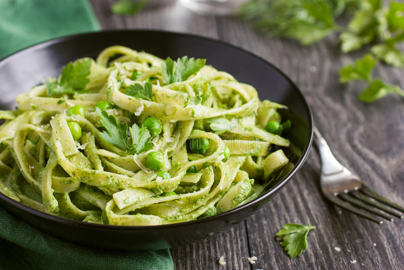 Massa dos tagliatelle com pesto dos espinafres e das ervilhas verdes fotografia de stock royalty free