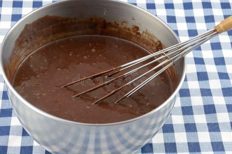 Massa e batedor de ovos do chocolate no recipiente foto de stock royalty free