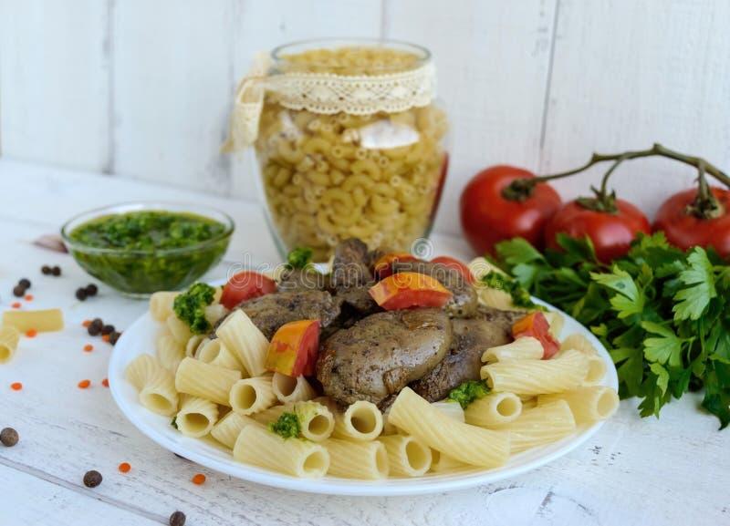Massa e fígado de ganso fritado (galinha, pato) com pesto e tomate em um fundo branco fotos de stock