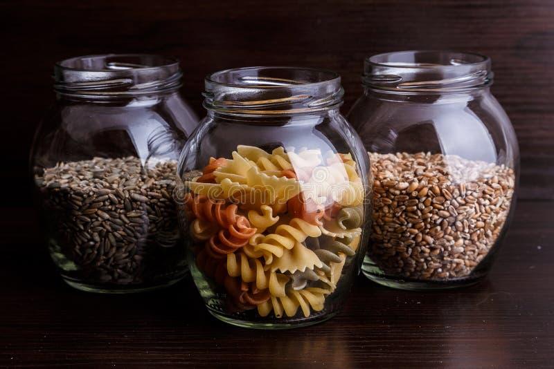 Massa e grões do trigo seco em um frasco no macro de madeira escuro do close-up do fundo fotografia de stock royalty free