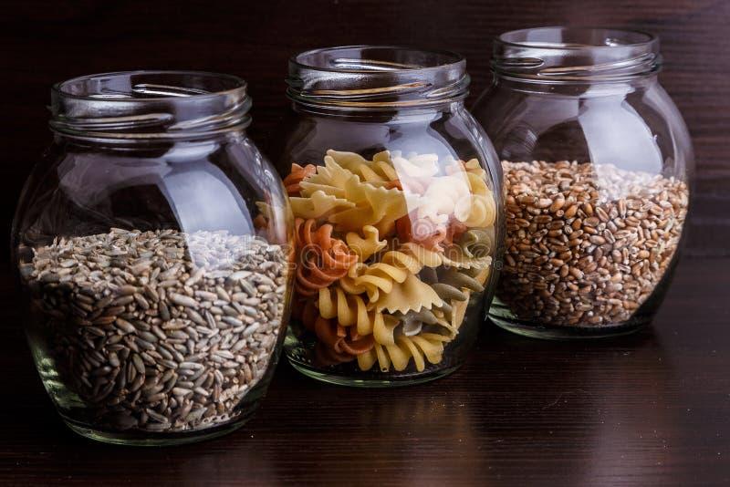 Massa e grões do trigo seco em um frasco no macro de madeira escuro do close-up do fundo foto de stock
