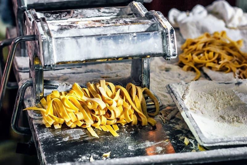 Massa e máquina frescas da massa na mesa de cozinha Fettuccine caseiro Processo de fazer o linguine caseiro da massa imagens de stock