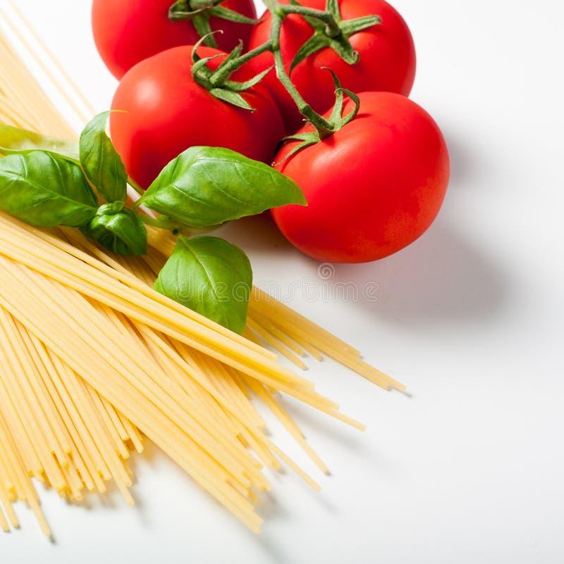 Massa e tomates dos espaguetes com folha da manjericão fotografia de stock