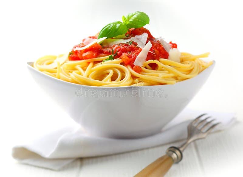 Bacia de massa com molho de tomate e manjericão fresca imagem de stock