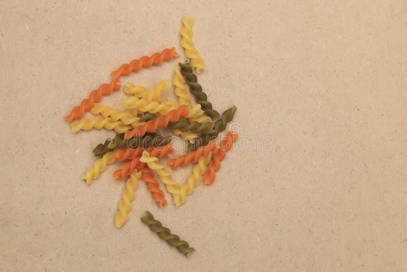 A massa espiral crua da torção de três cores dispersou no fundo marrom da madeira compensada foto de stock