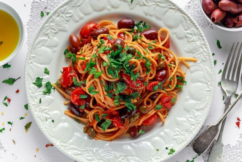 Massa italiana Alla Puttanesca do vegetariano com alho, azeitonas, alcaparras com na placa branca imagem de stock