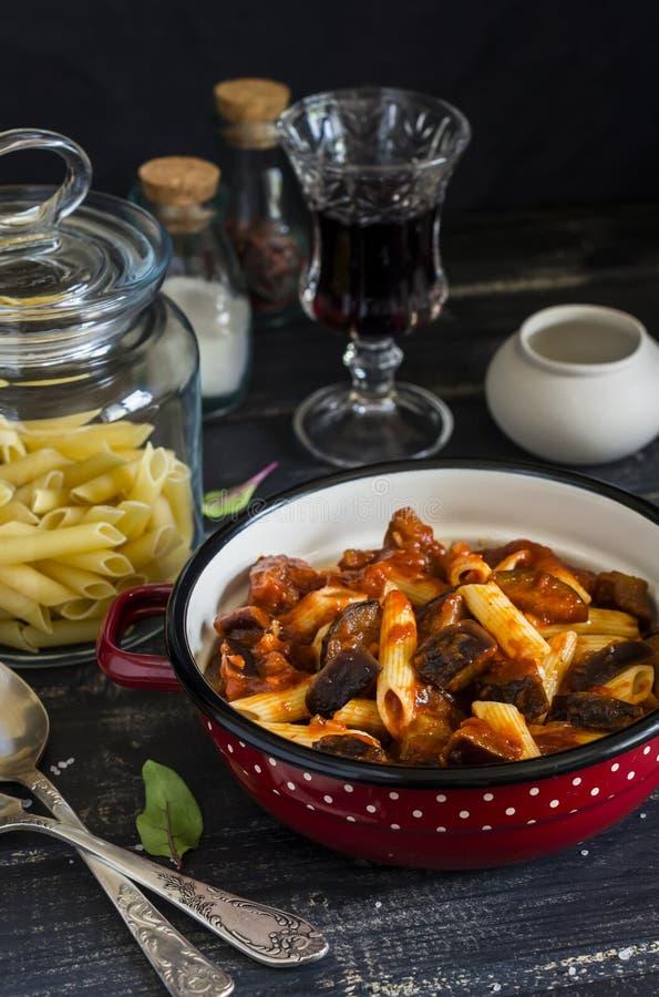 Massa italiana com molho da beringela e de tomate e um vidro do vinho tinto Em um fundo de madeira escuro imagem de stock