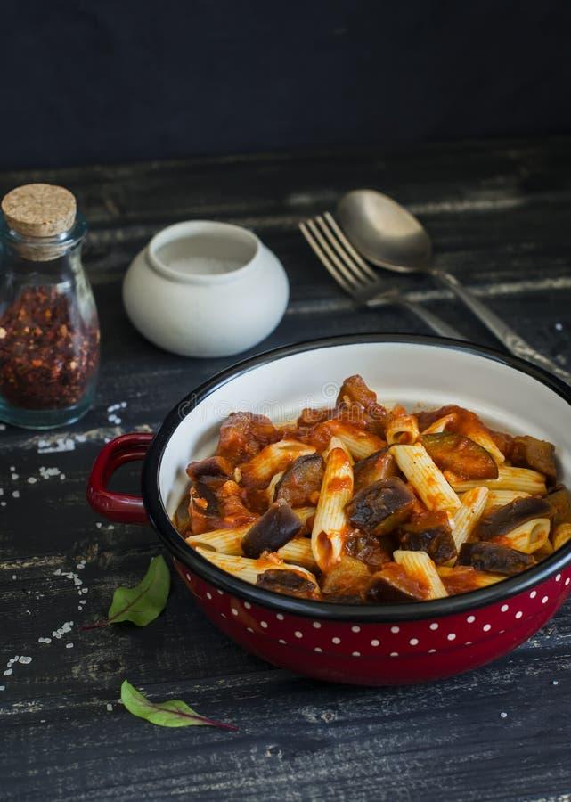 Massa italiana com molho da beringela e de tomate Em um fundo de madeira escuro imagens de stock