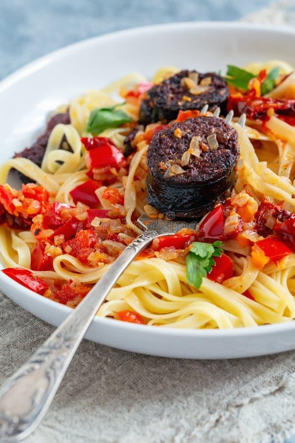 Massa italiana com molho de tomate e salsichas de sangue fotografia de stock