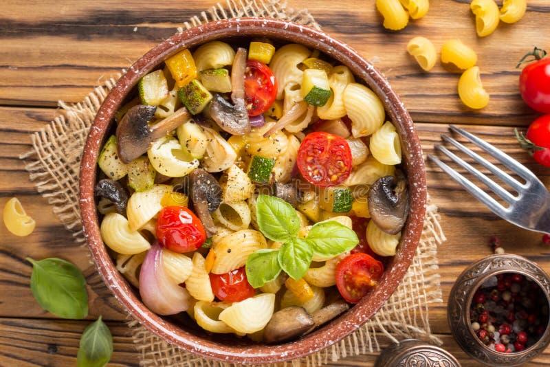 Massa italiana com vegetais e cogumelos fritados, abobrinha, tomates de cereja, cogumelo, queijo e manjericão Na bacia escura em  imagens de stock royalty free