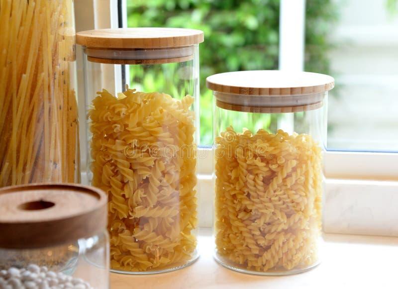 Massa italiana cru nas garrafas de vidro na tabela de madeira na cozinha com janela fotografia de stock royalty free