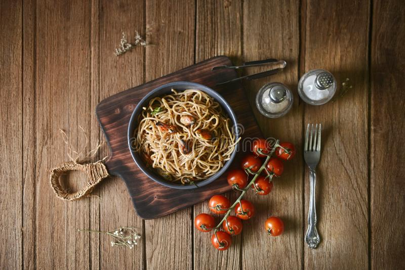 Massa italiana saboroso dos espaguetes com mexilhão, tomate e guarnição no prato redondo e a placa de madeira para servir na tabe imagens de stock