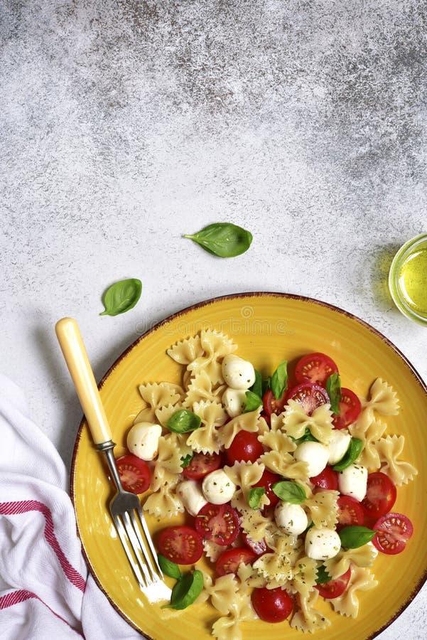 Massa italiana tradicional caprese: farfalle, bolas da mussarela, tomate de cereja e manjericão Vista superior com espaço da cópi foto de stock royalty free
