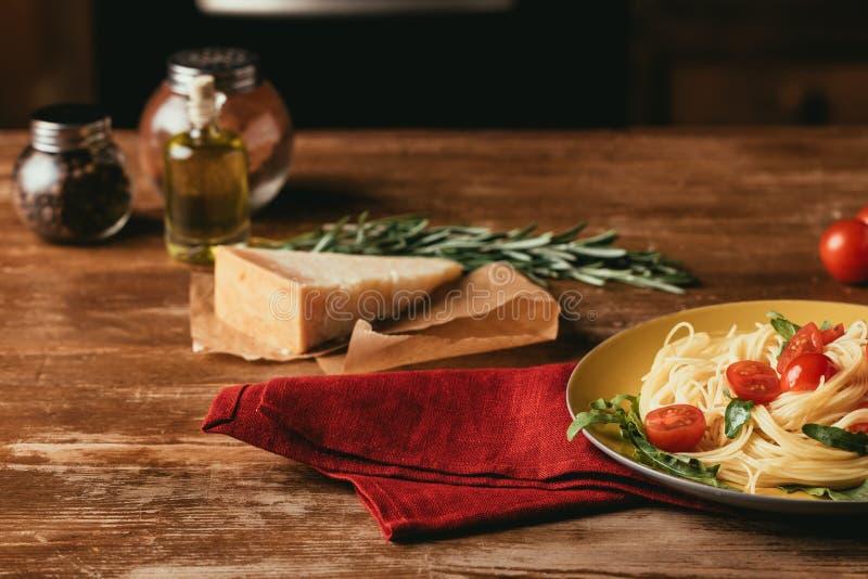 massa italiana tradicional com tomates e rúcula na placa na tabela de madeira com Parmesão, alecrim imagens de stock royalty free