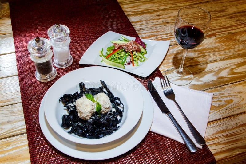 A massa preta dos chocos com salada, vinho, varas de pão na tabela de madeira, estabelece-se Vista de acima imagem de stock