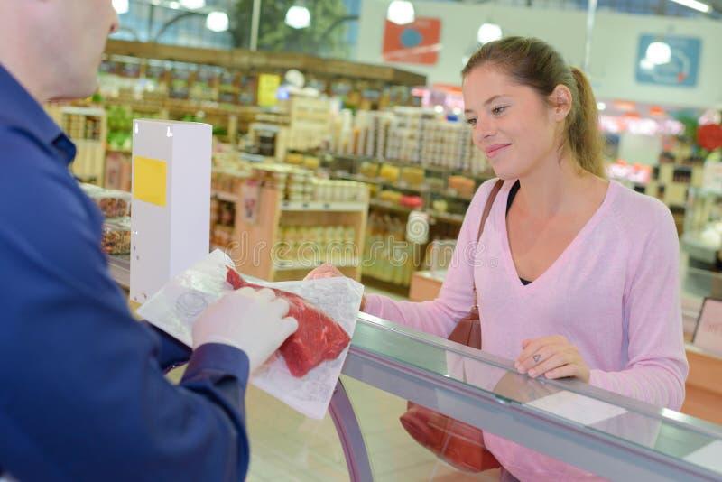 Massacre mostrar a carne vermelha ao cliente fêmea na loja imagens de stock