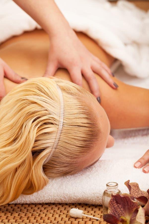 Massage and aromatherapy. Woman enjoying massage and aromatherapy royalty free stock photos