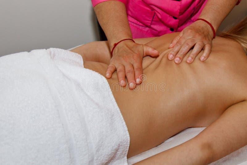 Massage arrière thérapeutique professionnel Le docteur de femme masse la fille l'athlète dans une salle de massage Corps et soins photo stock
