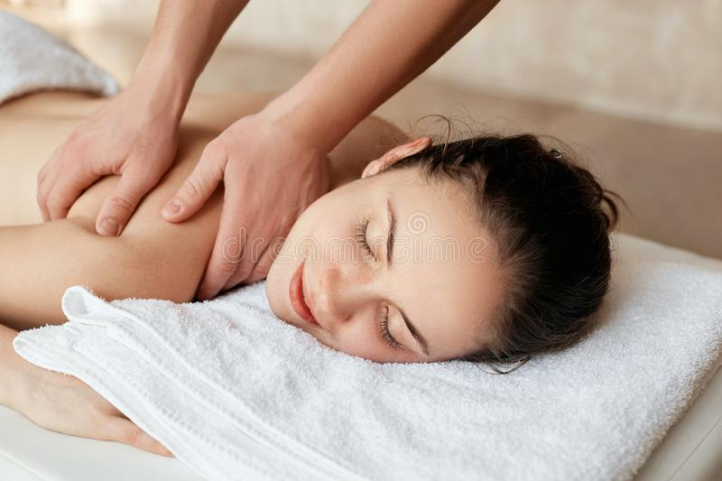 Massage. Beautiful woman  relaxing in spa salon. Body care. Spa body. Cosmetology. Girl having massage in the spa salon.  stock images