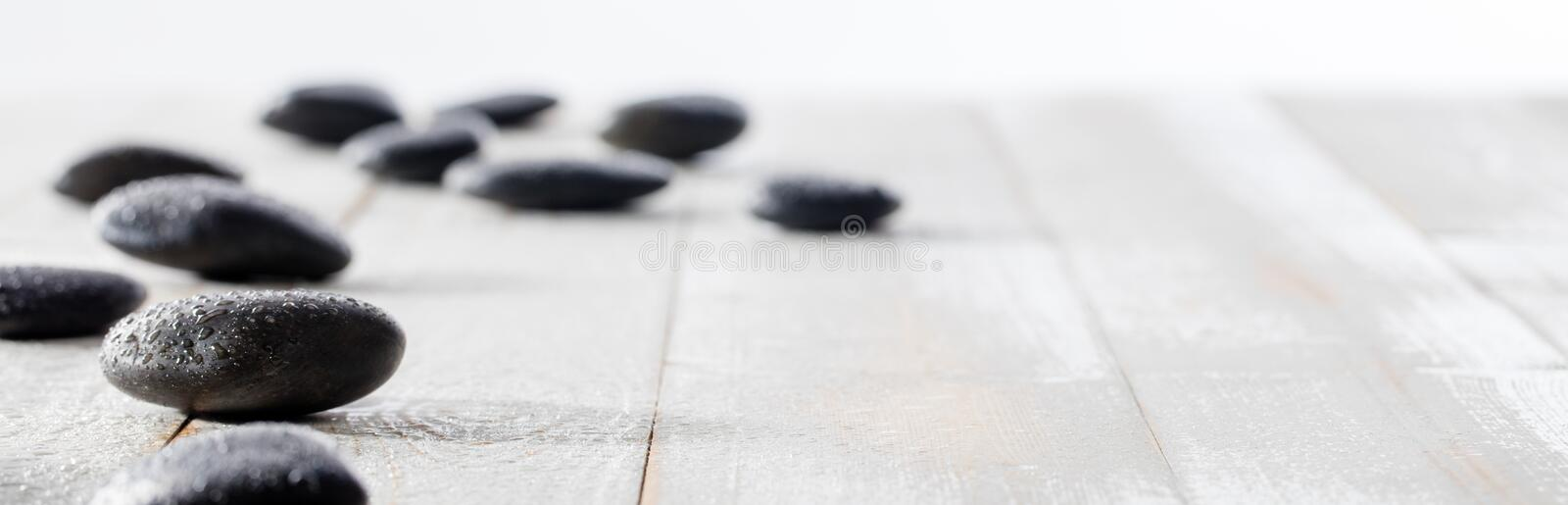 Massage black pebbles for spirituality, ayurveda, beauty spa or yoga. Massage black pebbles set on white wooden background for spirituality, ayurveda, beauty spa royalty free stock photo