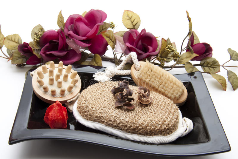 Massage brush with nailbrush. And sponge on black plate stock image