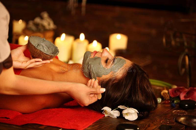 Massage and clay facial mask in spa salon. Young woman lying on wooden spa bed. Massage and clay facial mask in spa salon. Girl on candles background in massage royalty free stock images