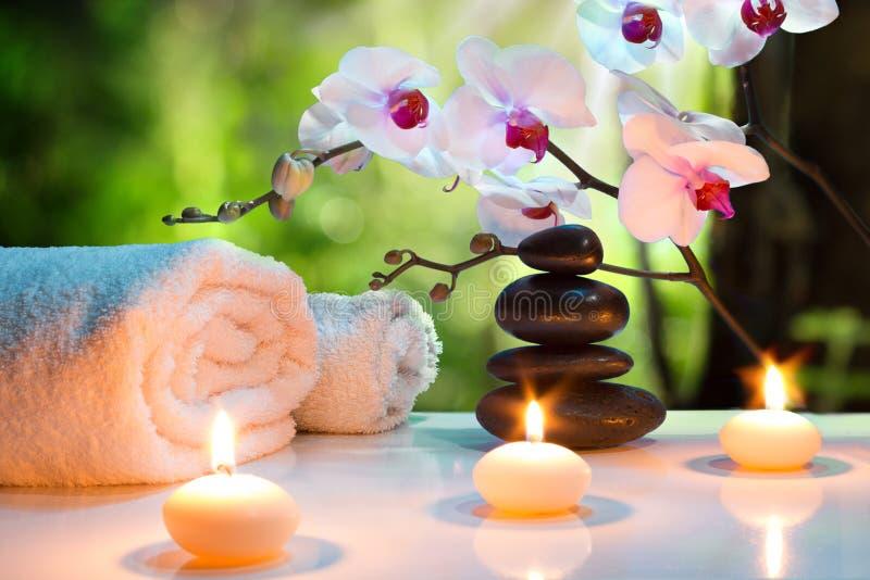 Massage composition spa met kaarsen, orchideeën en zwarte stenen in tuin royalty-vrije stock afbeeldingen