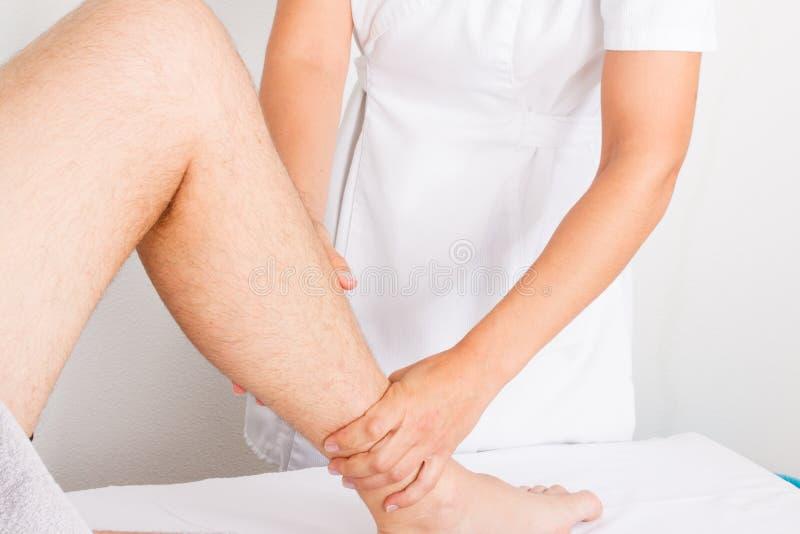 Massage d'homme de jambe par le thérapeute de femme photo libre de droits