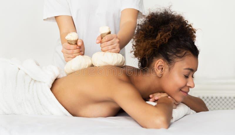 Massage de fines herbes Femme d'Afro appréciant le massage arrière chaud photos libres de droits