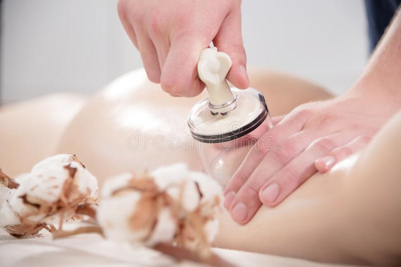 Massage de la cuisse anti-cellulite à l'aide de bidons à vide Un homme met la boîte à vide du physiothérapeute sur une femme photos stock