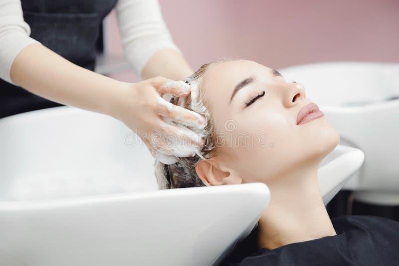 Massage de la tête de conception Belle femme blonde se laver les cheveux dans un salon de beauté photo stock