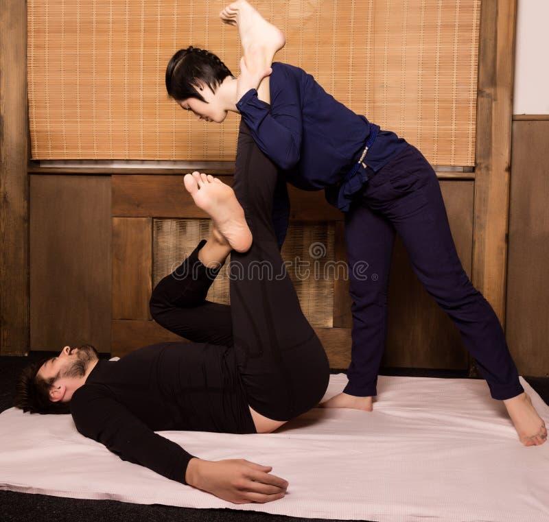 Massage de pied dans le studio thaïlandais Thérapeute professionnel donnant le massage thaïlandais traditionnel photographie stock libre de droits