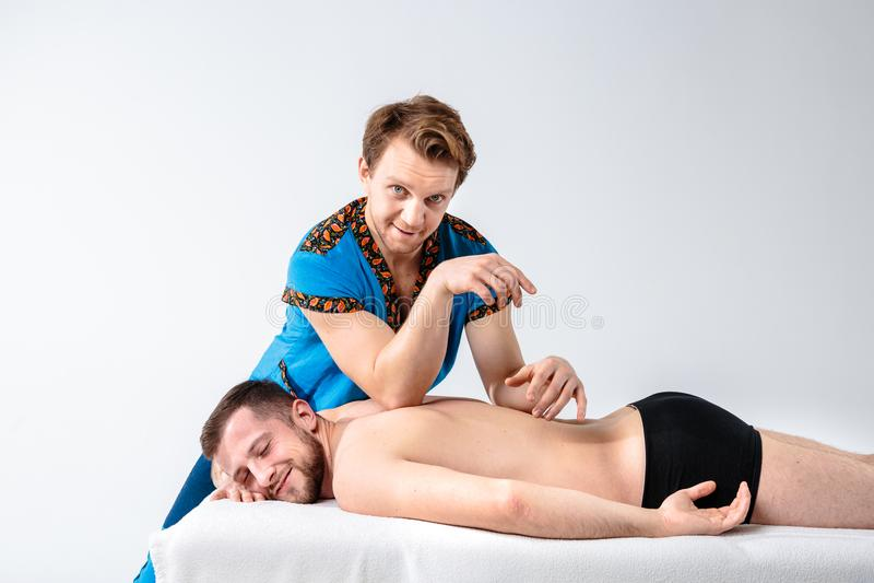 Massage de thème et soin de corps Le bel homme caucasien dans l'uniforme bleu et la barbe faisant l'étirage, guérit, diagnostic d photo libre de droits