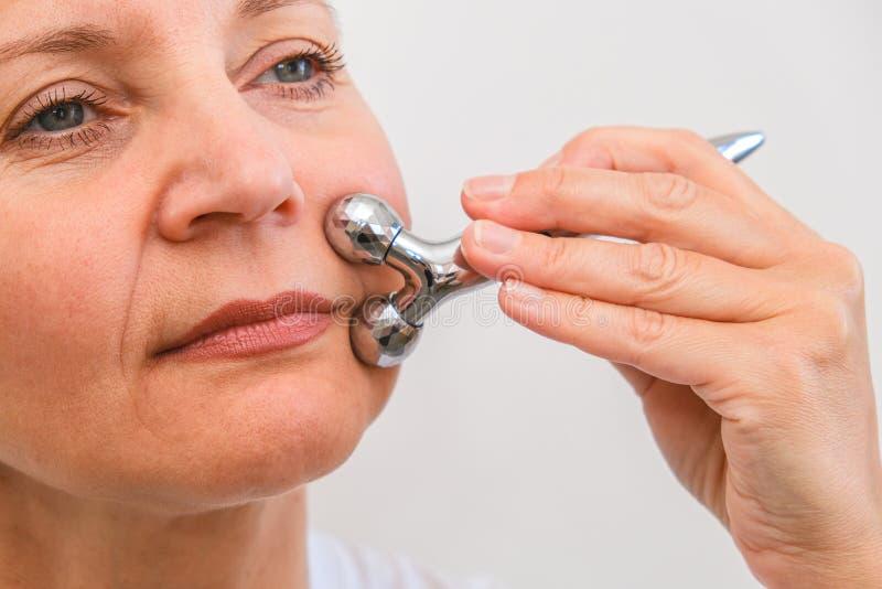 Massage de visage dans le macro d'environnement de station thermale Femme attirante avec les yeux ?troits faisant des soins de la image libre de droits