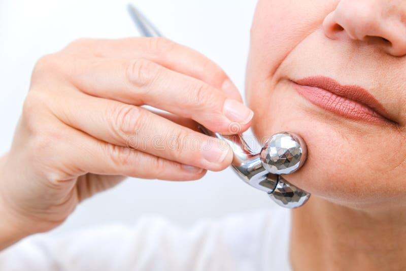 Massage de visage dans le macro d'environnement de station thermale Femme attirante avec les yeux ?troits faisant des soins de la images libres de droits